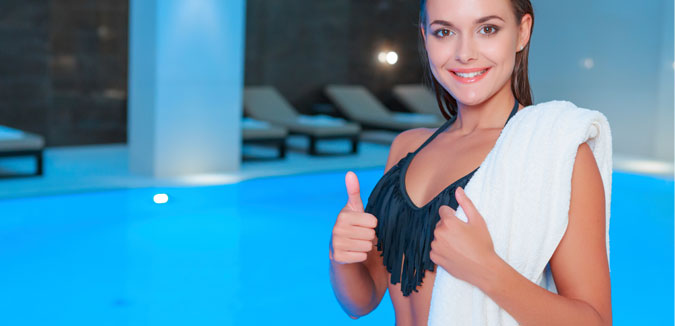 Licensed Bravo Bra Pads blog image of swim shapers girl with white towel and fringe bikini giving a thumbs up by the indoor pool.